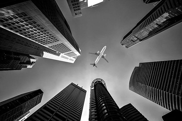 low angle view of buildings with airplane composition tip leading lines