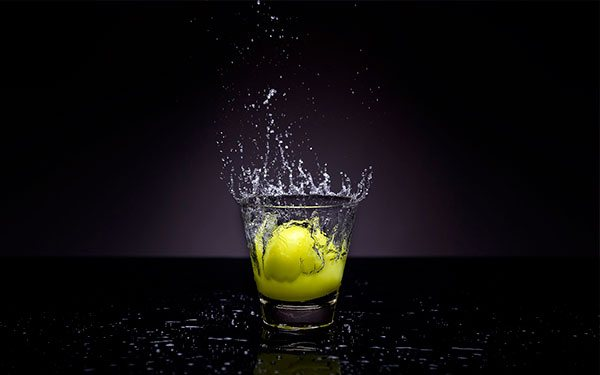 lemon dropping in glass water splash high speed photography